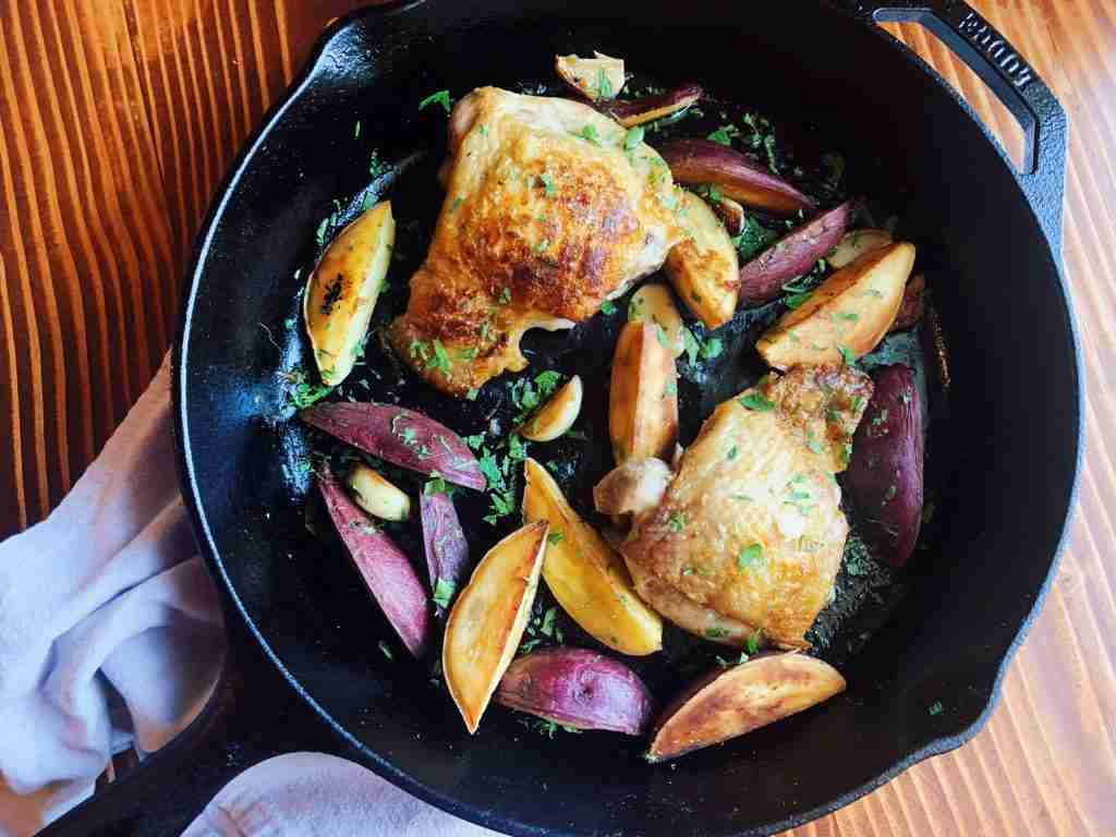 One-pan chicken thighs with sweet potatoes, garlic, and parsley in a cast-iron skillet