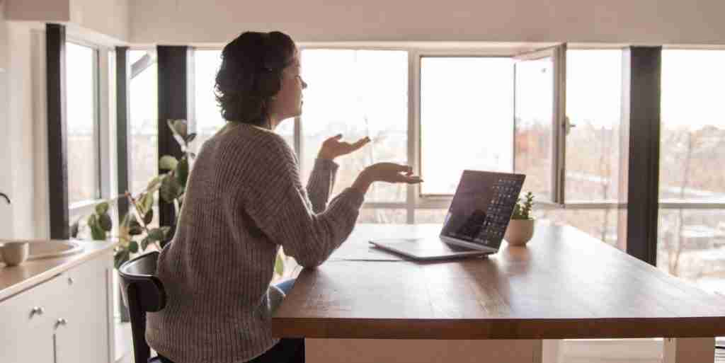 Woman sitting talking to a laptop in her kitchen. My virtual nutrition counseling for eating disorders and disordered eating can help you break free from diet culture.