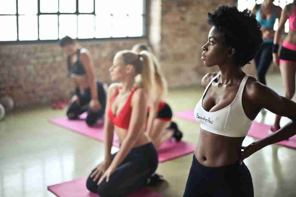 Photo of a black woman and a white woman in a group fitness class. 75 Hard review by a registered dietitian: There are no benefits and so many risks to this diet challenge.