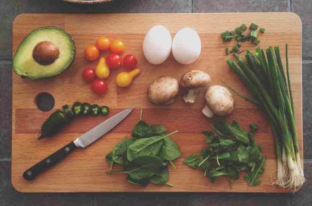 Vegetables and eggs on a cutting board with a knife. Whole30 won't lead to food freedom.
